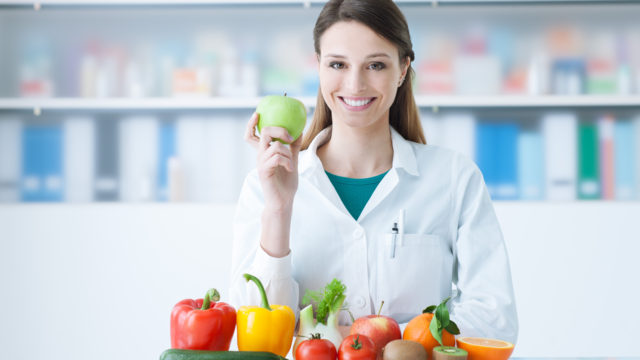 Nutritionist holding up an apple